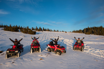 Group of people sitting with hands up on four-wheelers ATV bikes in the the mountains in winter evening