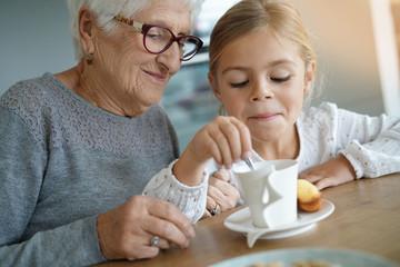 Little girl having tea time with grandma