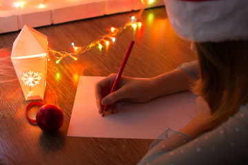 Cute girl writes a letter to Santa Claus near the fireplace and Christmas tree in the light of the garlands