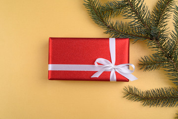 Christmas background with red gift box and fir tree branch on golden background, free space. Flat lay, top view with copy space