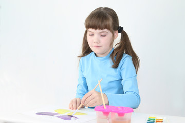 Happy girl watercolor paints butterfly on table in white room
