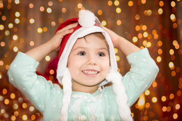 Child girl portrait in santa hat with christmas decoration, background with lights, face expression and happy emotions, winter holiday concept