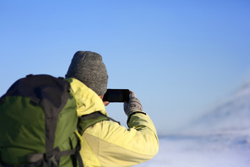 Back view of unrecognizable male in hat and backpack taking picture of amazing winter landscape