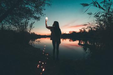 Ragazza immagina il futuro di fronte a un lago al tramonto