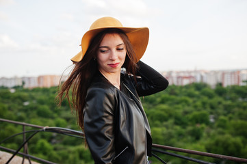 Portrait of a fabulous young woman in casual clothing posing with an orange hat.