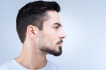Nice haircut. Calm unemotional young man standing quietly and showing his new haircut after visiting a qualified barber