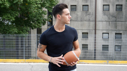 Handsome young man standing on street and holding American football ball.