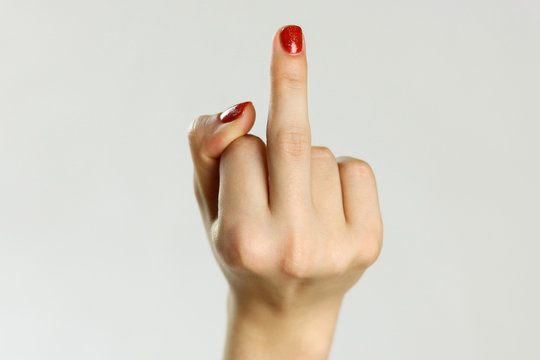 Female hand shows middle finger. Isolated on gray background. Closeup