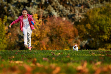 girl run in a park with a puppy jack russell terrier.