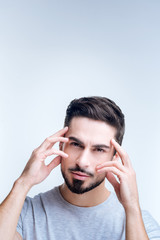 Different view. Talented young creative designer looking concentrated while standing against the blue background and touching his forehead with his fingers