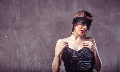 Sexy wet brunette girl wears black mask and top under rain drops on grey background with copyspace