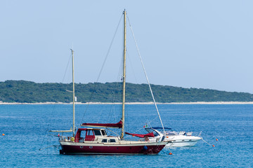 Old wooden sailboat ship is moored in calm sea.