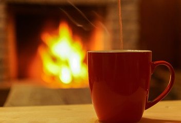 Cup of tea or  coffee on fireplace bokeh background.