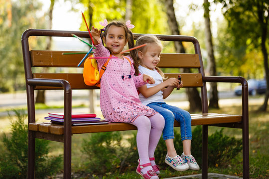 Adorable little school girl with pencils outdoor.