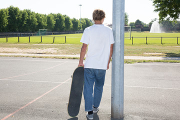 Blond teenage boy relaxed with skateboard under arm hand