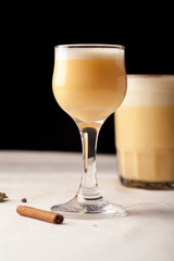Two glasses with christmas eggnog drink decorated with cinnamon on dark background. Vertical composition.