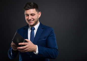 Elegant man in suit standing and checking his wallet