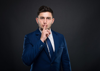 Handsome businessman doing silence gesture