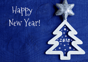 happy new yearwhite christmas tree with 2018 number on dark blue wooden background