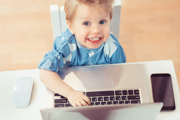 Top view of 2 years old Child working and printing on computer or laptop. View on laptop screen with free text place.