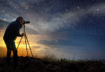 man taking a photo at dawn with starry sky