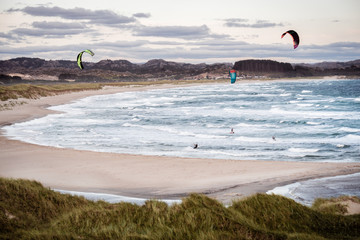Kitesurfing men in action on stormy sunset evening at Brusand Beach, Norway.