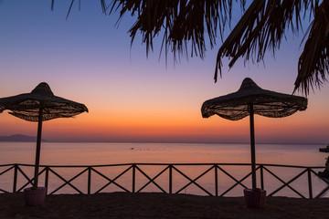 Beach umbrellas on the sand beach at dawn