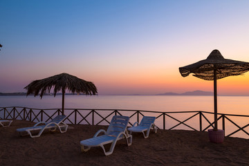 Beach umbrellas and sun lounger  at sunrise