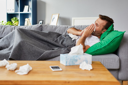 Sick man lying on sofa at home and blowing nose