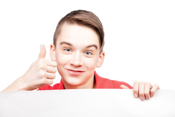 Teen boy holding blank banner or board on white showing thumb up