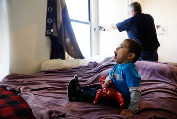 Natalia Rollins children Noah,2, yawns as Bob Friedl, a senior project manager with Environmental Management Solutions of New York Inc., checks lead levels with an X-Ray fluorescence detector at their apartment in the Coney Island section of the Brookly