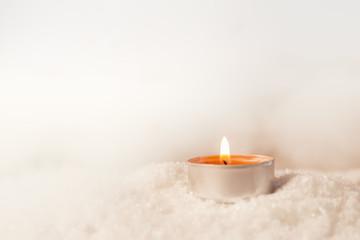Brennendes Teelicht im Schnee mit weißem Hintergrund und Lichter Bokeh