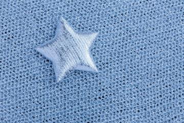 Shiny silver star on gray texture cloth