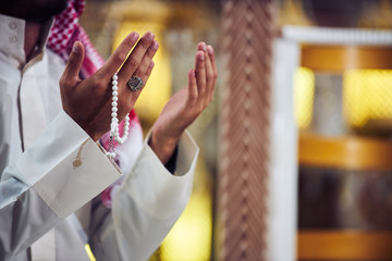 Hands holding tasbih of a religious man praying inside the mosque