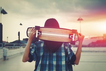 Young hipster woman holding skateboard behind head in cinematic style