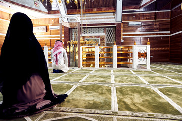 Two religious young people praying inside the mosque
