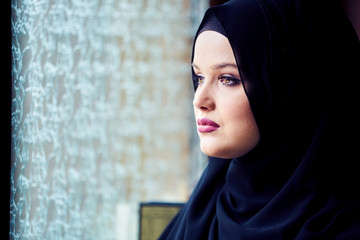 young woman wearing hijab looking out the window at mosque