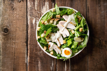 Classic Caesar salad with grilled chicken breast and half of egg in white ceramic plate. Served with croutons and dressing over old wooden background. Top view, space.