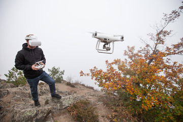 Young man handling drone, using virtual reality glasses.
