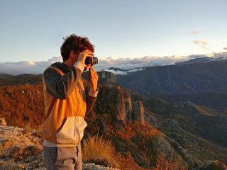 Man taking picture of sunset in mountains