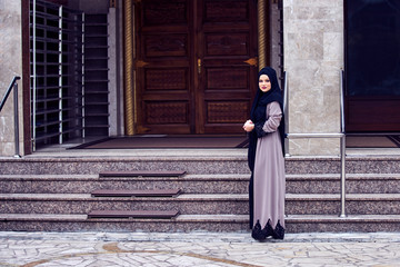 Portrait of a young religious woman wearing hijab in fron of mosque door