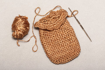 crocheting of viscose products, a small golden bag, a phone case, a golden thread with a metallic luster