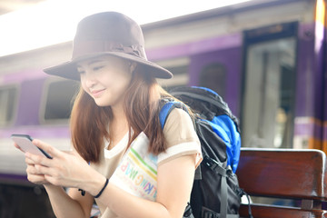 Asian woman is smiling while using smartphone chatting at the railway station during vacation trip.