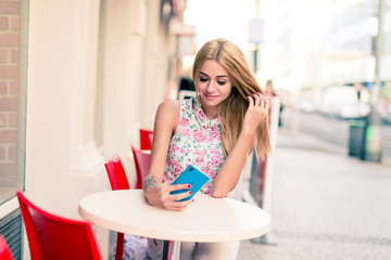 Girl blonde is sitting at an empty table of a street cafe with a smartphone in her hand