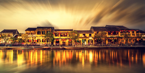 Street view with traditional boats on a background of ancient town in Hoi An Vietnam