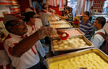 Customers purchase 'Rosogolla', popularly known as the king of Indian sweets, inside a sweet shop in Kolkata