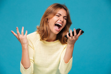 Angry woman in sweater screaming at smartphone