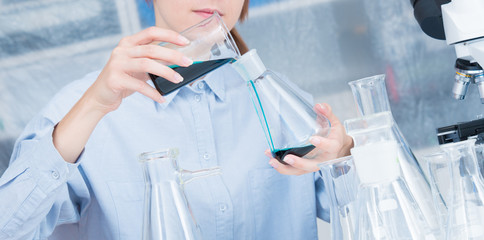 A female laboratory assistant mixes reagents in a chemical laboratory