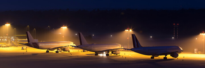 passenger airplanes waiting on an aiport at night