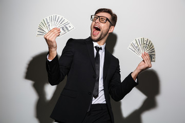 Overjoyed bearded man in black suit holding two bunches of dollars banknotes